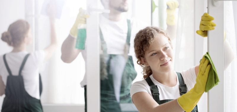 A smiling woman in yellow gloves washing a window frame with coworkers
