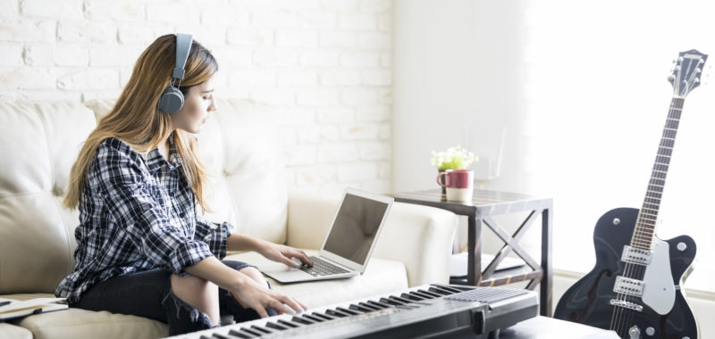 Pretty young woman sitting on sofa wearing headphones composing music using laptop and piano at home
